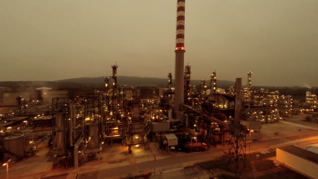 Industrial Background of Oil and Gas Refinery Factory. Global Warming Symbol Aerial View of Oil Plant with Smokestack at Night. oil and gas stock videos & royalty-free footage