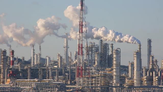 stockvideo's en b-roll-footage met industriële achtergrond van roken raffinaderij plant. - olieraffinaderij