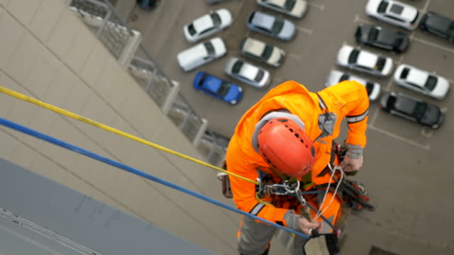 vídeos de stock, filmes e b-roll de alpinista industrial de terno e capacete prepara configurações de banda de rodagem protegê-lo de esfregar contra carros de fundo - alto descrição geral