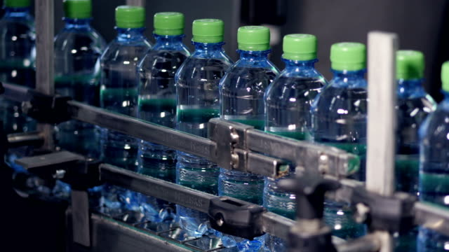 Industrial conveyor transporting plastic bottles with water. video