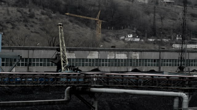 industrial cranes loading coal cranes loading coal at post apocalyptic looking industial area crane construction machinery stock videos & royalty-free footage