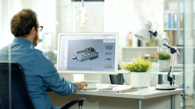 industriell designingenjör fungerar på en 3d komponent i cad-program på sin dator. han arbetar i en kreativ moderna kontor. - man architect computer bildbanksvideor och videomaterial från bakom kulisserna