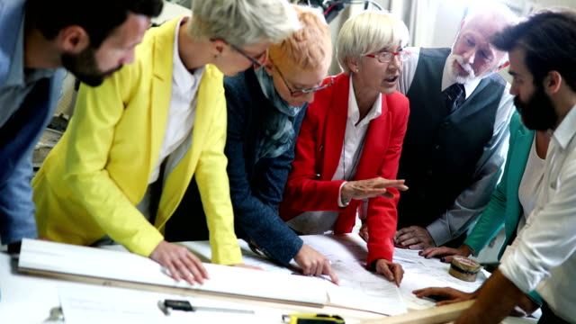 Industrial design team in a meeting. Closeup of mixed age people of industrial design department at a factory. They are gathered at a desk in large production facility and discussing certain blueprints and documents. One of the senior women is leading this very serious business discussion. There are four women and three men. 4k video. businesswear stock videos & royalty-free footage