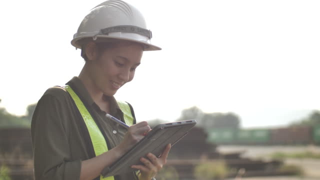 Industrial Engineer Asian Female in Hard Hat Wearing Safety Jacket Uses Touchscreen Tablet Computer