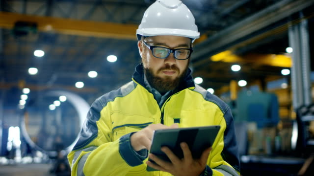 industrial engineer in hard hat wearing safety jacket uses touchscreen tablet computer. he works at the heavy industry manufacturing factory. - industria edile video stock e b–roll