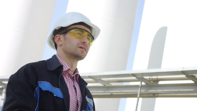 Industrial engineer in protective glasses and helmet outdoors video