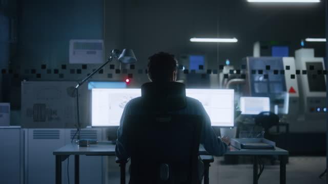 vídeos de stock, filmes e b-roll de engenheiro industrial resolvendo problemas, trabalhando em um computador pessoal, duas telas de monitor mostram software cad com protótipo 3d de conceito de motor elétrico ecológico. retroview zoom em - designer profissional
