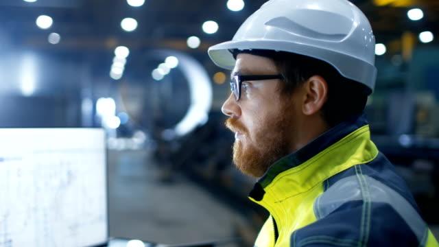 wirtschaftsingenieur tragen schutzhelm, sicherheitsweste und gläser lächeln vor der kamera. er arbeitet in großen schwerindustrie fabrik. - bauarbeiterhelm stock-videos und b-roll-filmmaterial