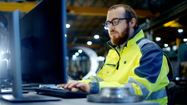 Industrial Engineer Works at Workspace on a Personal Computer.  He Wears  Safety Jacket and Works in the Main Workshop of the Heavy Industry Manufacturing Factory.