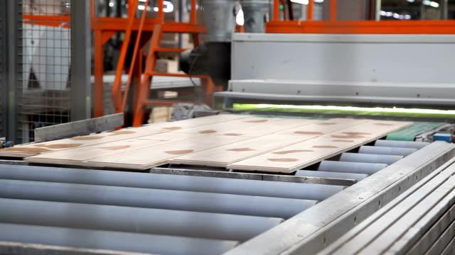 vídeos de stock e filmes b-roll de industrial equipment for the production of laminate. - material de construção