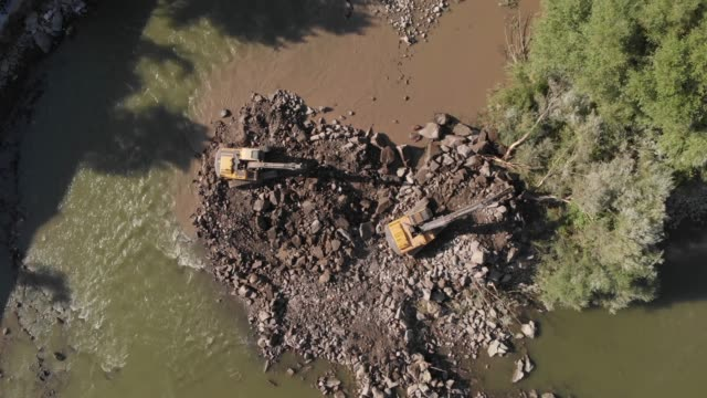 industrial excavator working in the river, extracting rocks and pebbles on construction site industrial excavator working in the river, extracting rocks and pebbles on construction site civil engineering stock videos & royalty-free footage