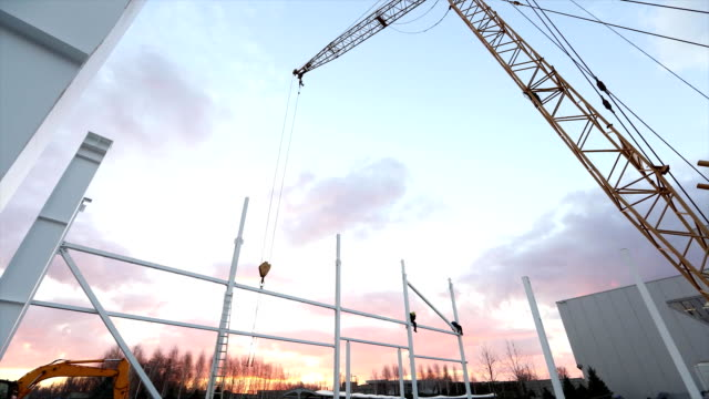 Industrial exterior, Mounting of metal structures against the background of an orange sky with clouds, construction work, construction of an industrial building, timelapse