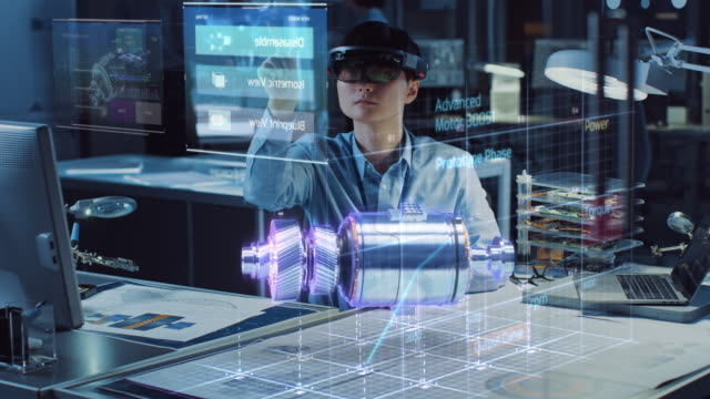Industrial Factory Chief Engineer Wearing AR Headset Designs a Prototype of an Electric Motor on the Holographic Projection Blueprint. Futuristic Virtual Design of Mixed Technology Application. video