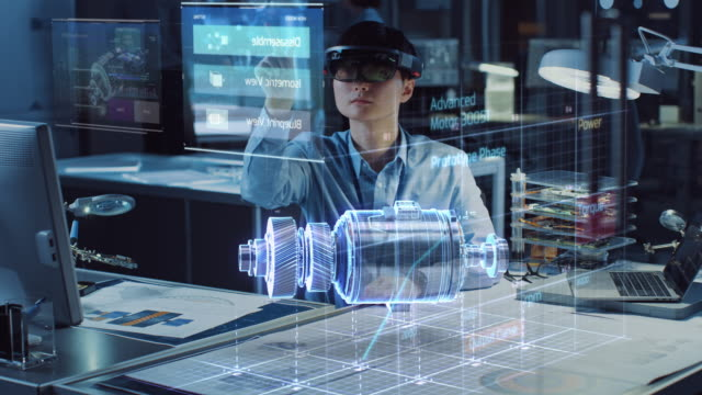 industrial factory chief engineer wearing ar headset designs a prototype of an electric motor on the holographic smart blueprint. futuristic virtual design of mixed technology application. - rzeczywistość witrualna filmów i materiałów b-roll