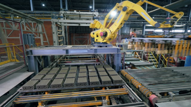 Industrial factory products are getting relocated by the automatic robot manipulator.