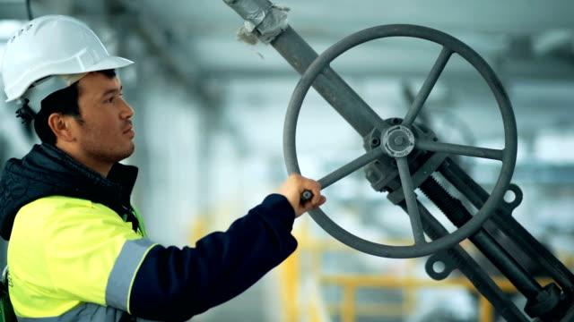 Industrial factory worker turning wheel of valve Industrial factory worker turning wheel of valve. biofuel stock videos & royalty-free footage