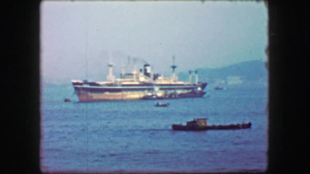 1944: Industrial harbor ship low profile tugboat traveling hazy harbor waters. video