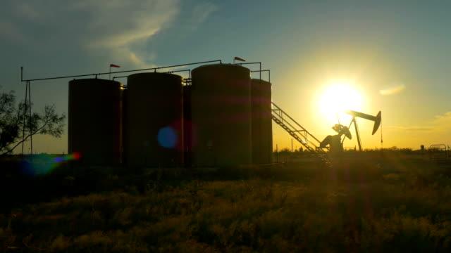 Industrial jack pump platform pumping crude oil against sunset sun video