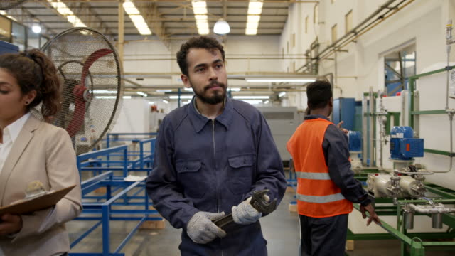 Industrial laborer walking through the manufacturing factory holding a wrench and people working at their stations