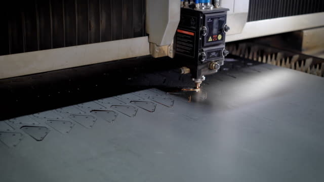 Industrial laser cutter with sparks. The programmed robot head cuts with the aid of a huge sheet of metal temperature. Modern machine improves quality and productivity video