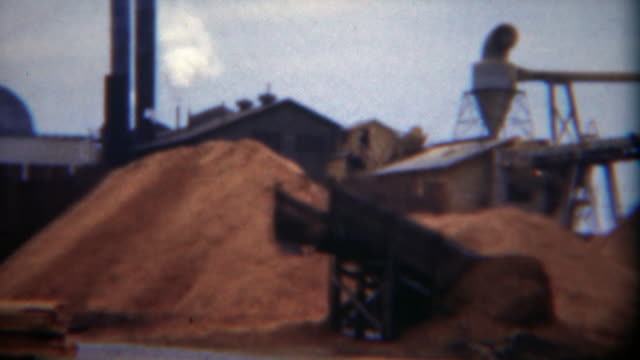 1949: Industrial lumber mill factory wood dust processing smokestack waste. video