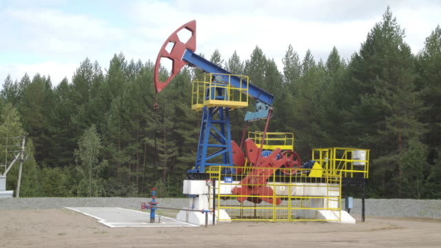 industrial oil pump jack working and pumping crude oil for fossil fuel energy with drilling rig in oil field. balancing drive rod pumps oil rocker. equipment for wellhead connection oil well. - opec video stock e b–roll