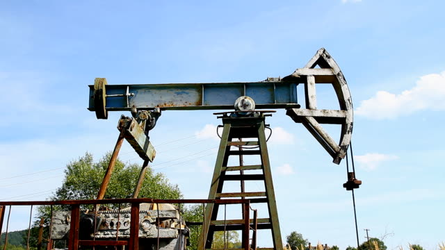 Industrial oil pump jack working and pumping crude oil