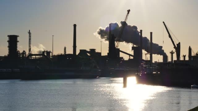 vídeos de stock e filmes b-roll de industrial plant with big smoke stacks and harbor - combustível fóssil
