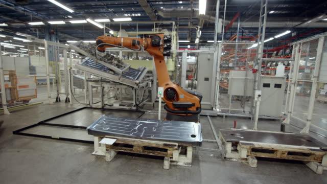 cs industrial robot moving molded aluminum plates in the factory - манипулятор робота производственное оборудование стоковые видео и кадры b-roll