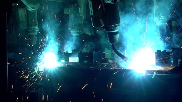 Industrial robots are welding automotive part in factory Industrial robots are welding automotive part in factory robot stock videos & royalty-free footage