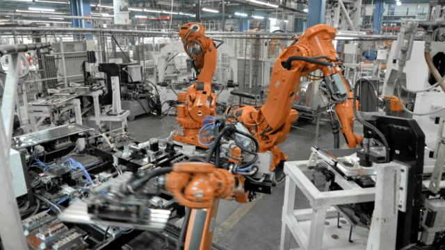LD Industrial robots assembling metal parts in a factory video