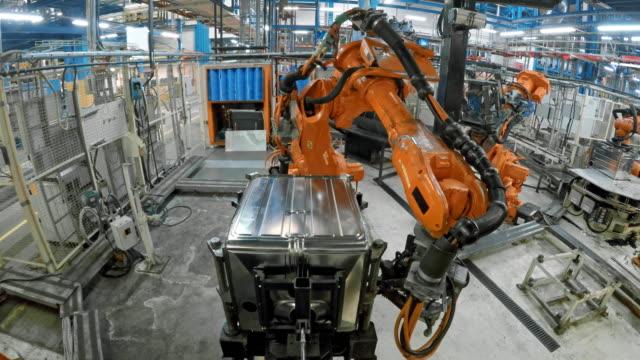 ld industrial robots attaching a metal frame on the base of a product - манипулятор робота производственное оборудование стоковые видео и кадры b-roll