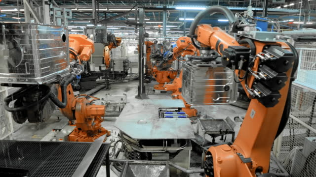 TIME-LAPSE Industrial robots in operation in a factory Wide locked down time-lapse shot of industrial robots performing their operations in a factory. Shot in Slovenia. robot stock videos & royalty-free footage