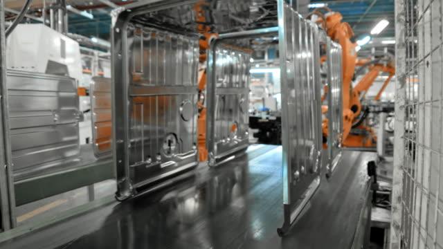 TIME-LAPSE Industrial robots placing metal frames onto a conveyor belt Wide locked down time lapse shot of industrial robots placing metal frames onto a conveyor belt in a factory. Shot in Slovenia. conveyor belt stock videos & royalty-free footage