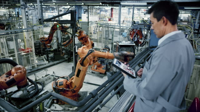 CS Industrial robots' work process being supervised by an Asian male engineer