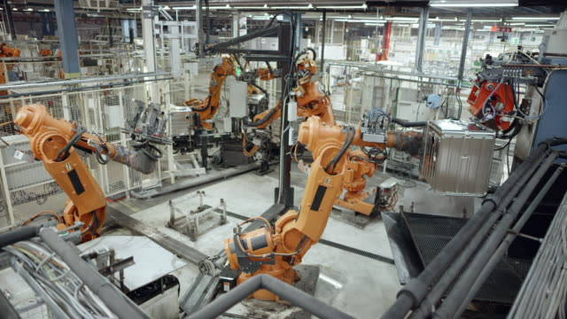cs industrial robots' work process in the factory - attrezzatura industriale video stock e b–roll
