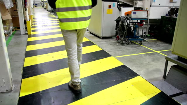 Industrial Safety Manager walking across yellow-black safety area inside the factory. Manger wearing high visibility jacket. warning sign stock videos & royalty-free footage
