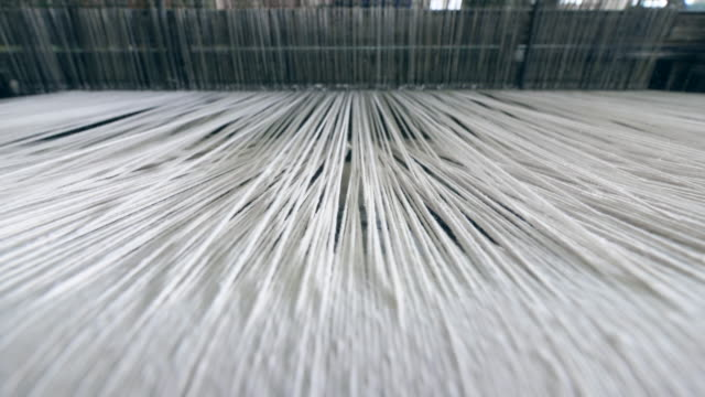 vídeos de stock e filmes b-roll de industrial textile factory. close up of thick white threads moving through the loom - têxtil