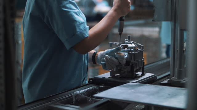 Industrial worker assembling metal appliances at automatical conveyor at factory Industrial worker assembling metal appliances at automatical conveyor at factory. Close up engineer detailing electrical devices at production line on plant work tool stock videos & royalty-free footage
