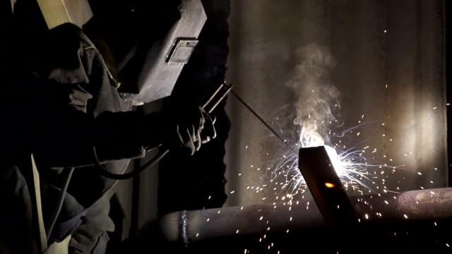 Industrial worker welding metal pipe