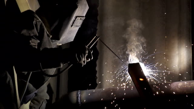 stockvideo's en b-roll-footage met industrial worker welding metal pipe - lassen