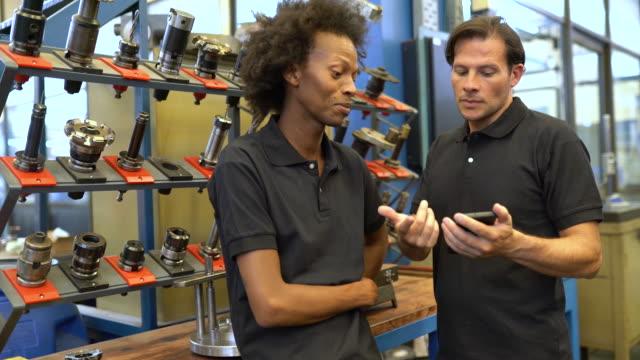携帯電話で新しいツールデザインを議論する産業労働者 ビデオ