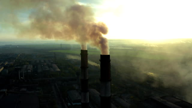 Industrial zone with a large red and white pipe thick white smoke is poured from the factory pipe in contrast to the sun. Pollution of the environment: a pipe with smoke. Aerial view