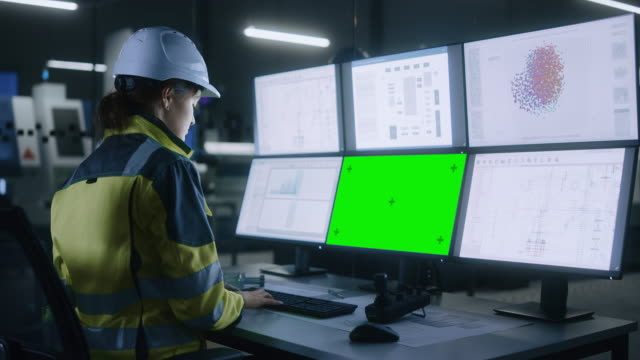 industry 4.0 modern factory: confident female operator controls facility, uses computer with multiple screens including: green screen / chroma key, ai concept, machine learning ui - azionare video stock e b–roll