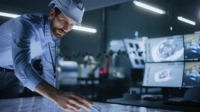 industrie 4.0 moderne fabrik büro tagungsraum: schöne männliche ingenieur trägt hardhat, verwendet stift auf touchscreen digital table zu korrigieren, zeichnen maschinen blaupausen. high-tech-elektronik-fazilität - it stock-videos und b-roll-filmmaterial