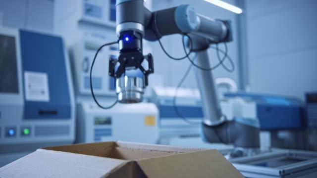 industria 4.0 modern factory: braccio robot programmato che impacchetta componenti metallici in scatola di cartone. la macchina della linea di produzione raccoglie il prodotto in confezione su trasportatore. robotica del magazzino completamente automatizza - metal robot in logistic factory video stock e b–roll