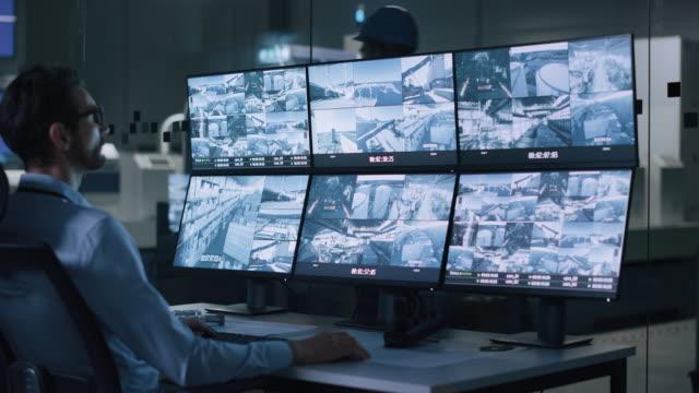 vídeos y material grabado en eventos de stock de industria 4.0 fábrica moderna: el operador de seguridad controla el funcionamiento correcto de la línea de producción del taller, utiliza el ordenador con pantallas que muestran la alimentación de material de la cámara de vigilancia. seguridad de alta - seguridad