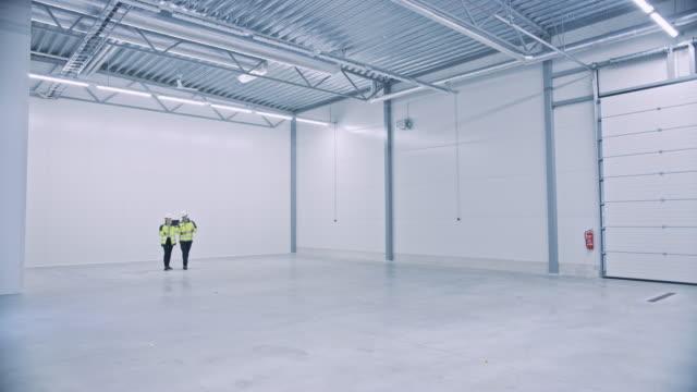 industrie 4.0 moderne fabrik: zwei ingenieure verwenden digitalen tablet-computer mit augmented reality software visualisierung der fertigungsanlagen raum mapping, factory layout. illustratives mock-up-konzept - halle gebäude stock-videos und b-roll-filmmaterial