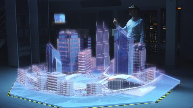 vídeos y material grabado en eventos de stock de industria 4.0: arquitecto profesional moderno que usa auriculares de realidad virtual utiliza gestos para mover, diseñar, manipular edificios para la ciudad 3d. software mixto de realidad aumentada. efecto visual especial vfx - copiar