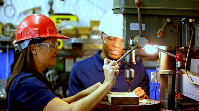Industry: Male and female workers at drill press Industry: Multi ethnic male and female at drill press in industrial workshop.  they wear hardhats,  safety goggles and uniforms. occupational safety and health stock videos & royalty-free footage